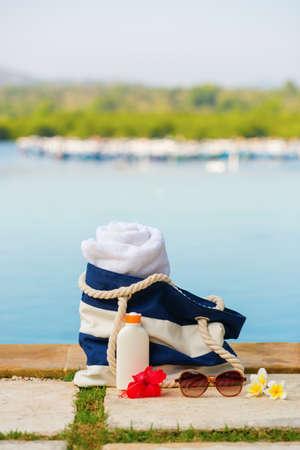 Beach bag, towel, sunscreen and sunglasses near the pool photo