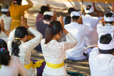 women praying: Young Balinese women praying in a temple during ceremony