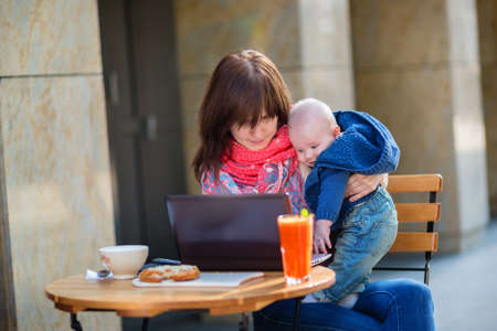 Young working mother with her little son in a cafe photo