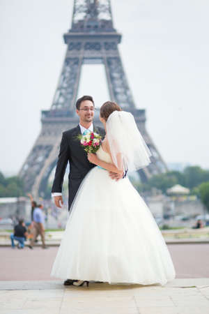 Happy just married couple near the Eiffel tower in Paris photo