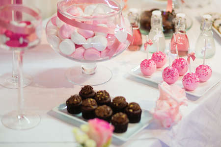horizontal bar: Pink cake pops on a dessert table at party or wedding celebration