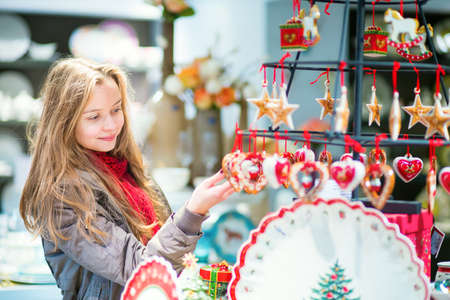 Young girl selecting Christmas decorations at Parisian Christmas market Stock Photo