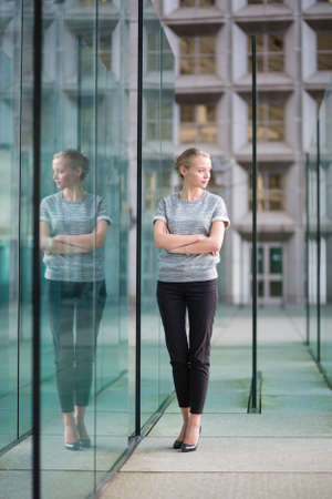 Young beautiful business woman in modern glass interior