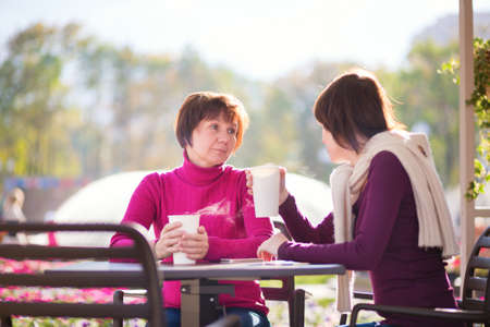 beautiful middle aged woman: Beautiful middle aged woman with her grown up daughter spending time together and talking in an outdoor cafe