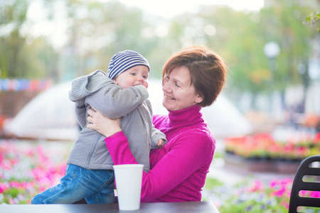 beautiful middle aged woman: Beautiful middle aged woman and her adorable little grandson having fun together in an outdoor cafe on a fall or spring day