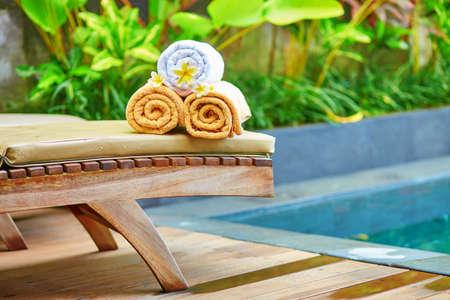 toalla: Toallas con flores frangipani blanco cerca de la piscina en un spa balin�s tradicional