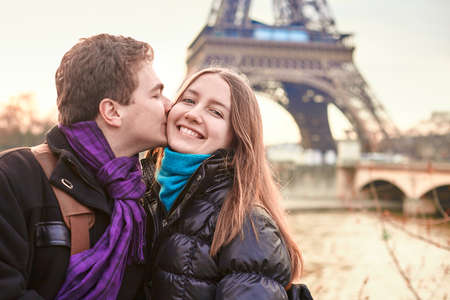 Beautiful young couple spending Valentines day in Paris together and kissing near the Eiffel tower photo