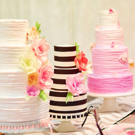 fancy cakes: Three different wedding cakes on a dessert table