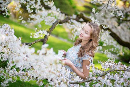 arbol de cerezo: Hermosa joven beber t� en jard�n de la cereza flor de un d�a de primavera Foto de archivo