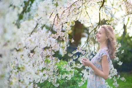 Mooi jong meisje in kersenbloesem tuin op een lentedag