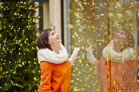 christmas lights display: Young girl looking at Parisian shop-windows decorated for Christmas