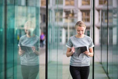 현대 유리 사무실 간 사용하여 태블릿에 웃는 젊은 여자
