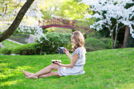 Beautiful young girl eating sushi in cherry blossom garden on a spring day photo