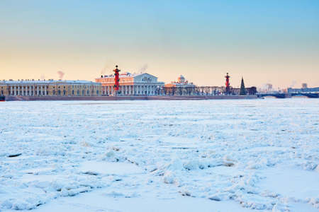 Scenic view of Rostral Columns and Spit of Vasilyevsky Island in St. Petersburg, Russia, on a beautiful winter day at sunset photo