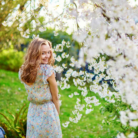 elegant dress: Beautiful young woman in cherry blossom garden on a spring day