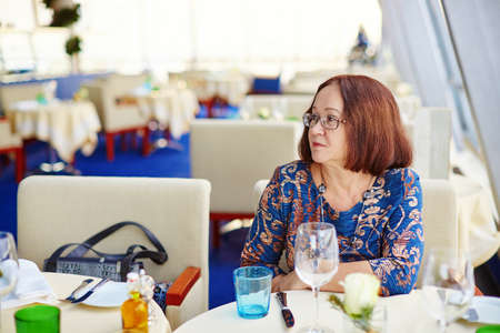 beautiful middle aged woman: Beautiful middle aged woman sitting at the table in restaurant