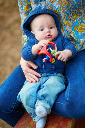 woman hanging toy: Adorable little baby boy playing with toy