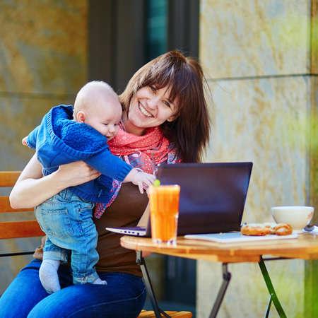 madre trabajando: Madre trabajadora joven con su peque�o hijo en un caf�
