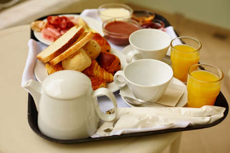 Delicious breakfast with fresh orange juice and pastry, focus on coffee cups photo
