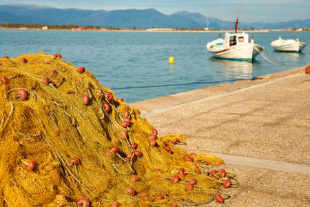 yellow boats: Pile of yellow fishing nets in port with boats in the background. Focus on fishing nets. Nafplion, Greece Stock Photo