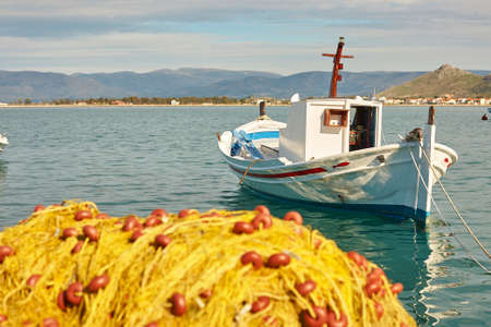 yellow boats: Pile of yellow fishing nets in port with boats in the background. Focus on boat. Nafplion, Greece