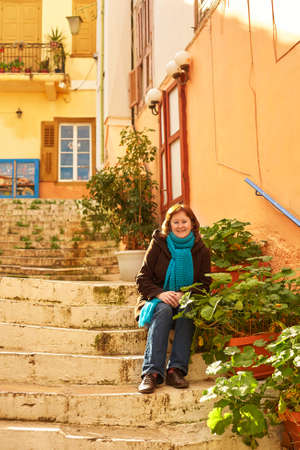 residental: Smiling girl in blue scarf sitting on the stairs on a street of Greek town Nafplion on a sunny winter day