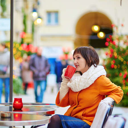 street cafe: Happy young girl drinking coffee in a Parisian street cafe on a fall, spring or winter day