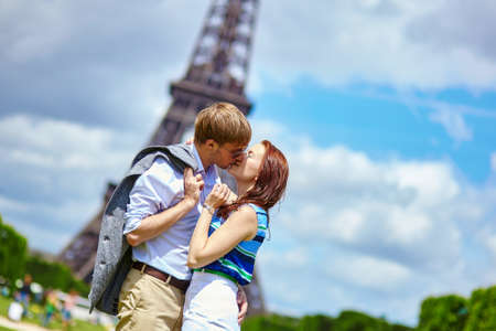 Romantic dating couple kissing in Paris near the Eiffel tower photo