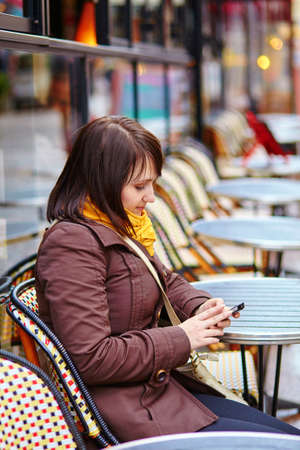 brune: Beautiful young tourist in Paris sending sms from Parisian street cafe
