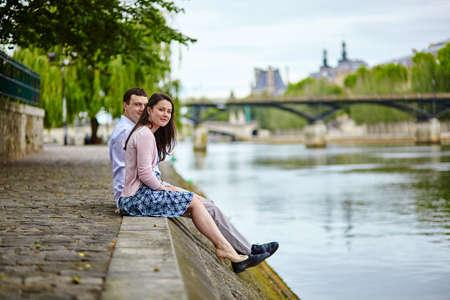 brune: Joyful couple is sitting on the embankment