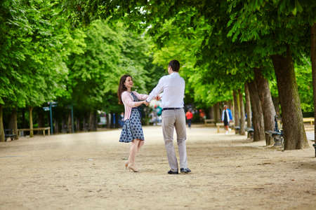 Dating romantic couple dancing in the Luxembourg garden of Paris photo