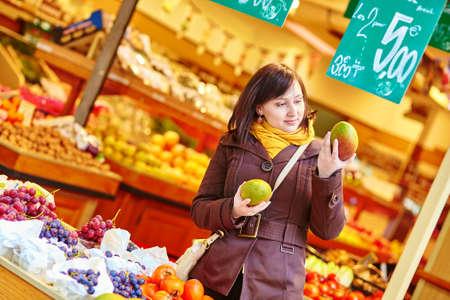 brune: Beautiful young woman buying fresh fruits at market Stock Photo