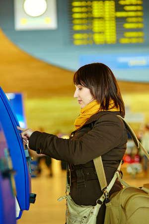 brune: Girl doing self-checkin in the airport before taking her flight