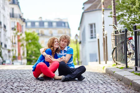 sitting on the ground: Young dating couple sitting on the ground and kissing