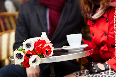 bunch of flowers: Happy couple having a date in cafe