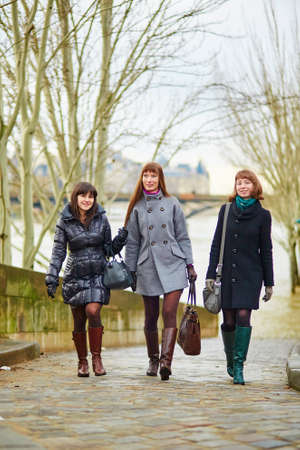 Three young cheerful girls walking together in Paris photo
