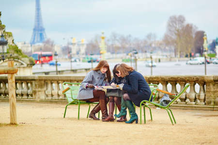 Tourists in Paris planning their trip using map photo