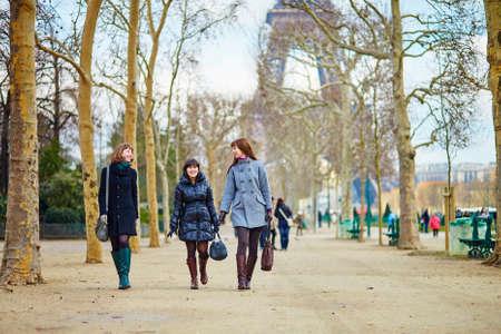 Three girls posing near the Eiffel tower photo