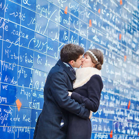 kissing couple: Romantic couple kissing near I love you wall in Paris Stock Photo