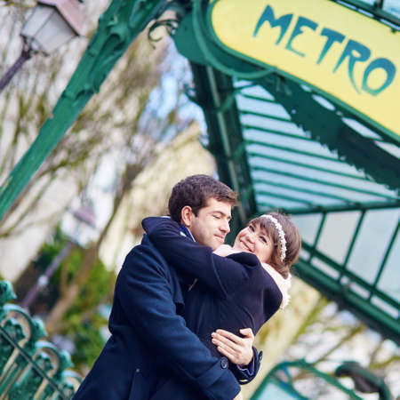 Happy young couple hugging near a subway station in Paris photo