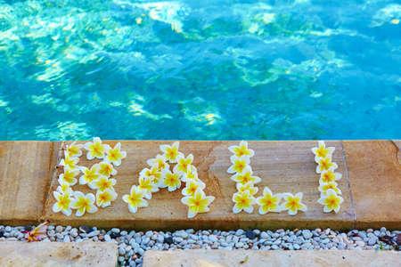 Word Bali geschreven met frangipani bloemen in de buurt van het zwembad