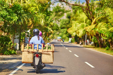 balinese: Balinese man with huge luggage on scooter Stock Photo