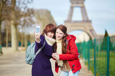 Two cheerful beautiful girls in Paris doing selfie near the Eiffel tower