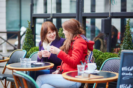 street cafe: Two beautiful young girls chatting in a Parisian street cafe Stock Photo