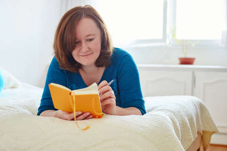 bad planning: Girl lying on the bad and writing into diary or planning her day Stock Photo