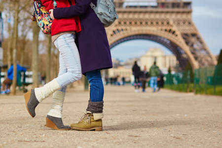 Closeup of female legs, two girls hugging on the street in Paris, same-sex relationship concept