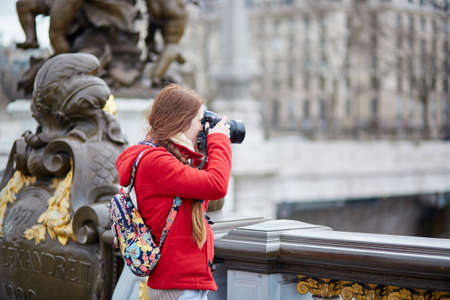 alexandre: Beautiful young tourist in Paris on the Pont Alexandre III, taking a photo Stock Photo