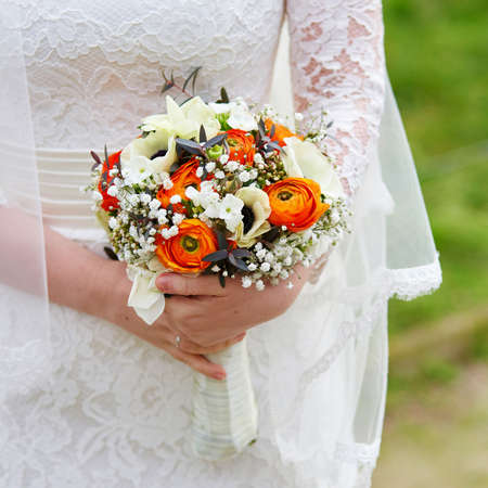Young bride holding beautiful wedding bouquet with orange ranunculus Stock Photo