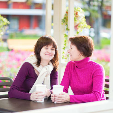 grown up: Beautiful middle aged woman with her grown up daughter spending time together and talking in an outdoor cafe
