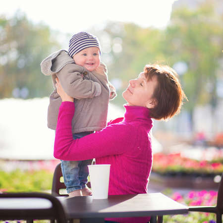 Beautiful middle aged woman and her adorable little grandson having fun together in an outdoor cafe on a fall or spring day